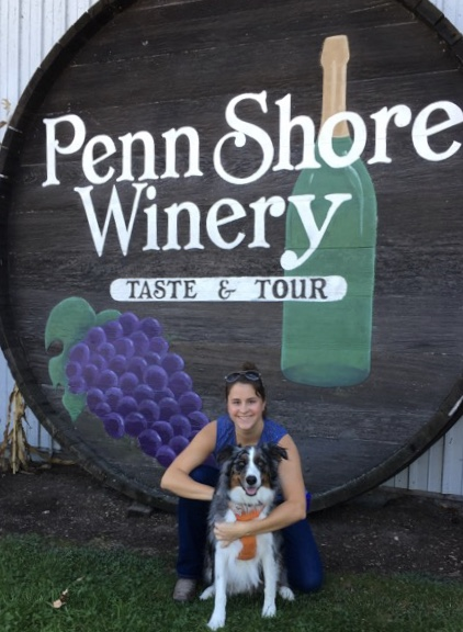 Young Lady with Dog In Front of Winery Sign